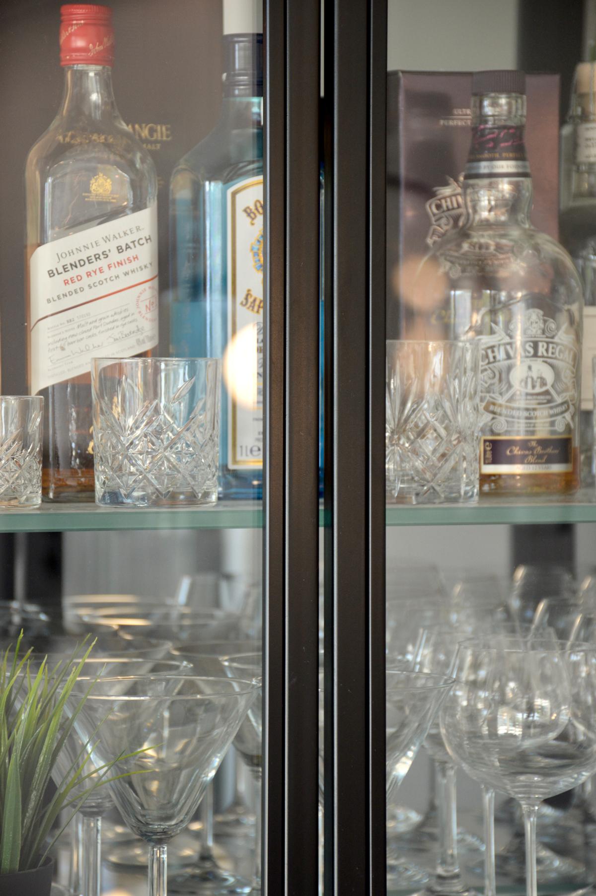 צילום מקרוב של ויטרינה מברזל שחור, דלתות ומדפי זכוכית